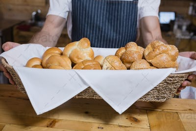 Mid section of waiter holding basket of baked pastries at counter