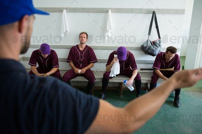Rear view of coach discussing with baseball team