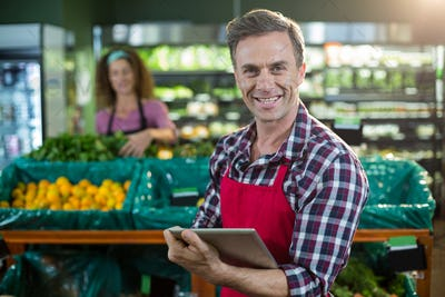 Smiling staff using digital tablet in organic section