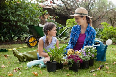 Smiling mother and daughter sitting with various potted plants
