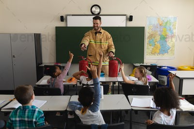 Schoolkids raising hands while male firefighter teaching about fire safety in classroom