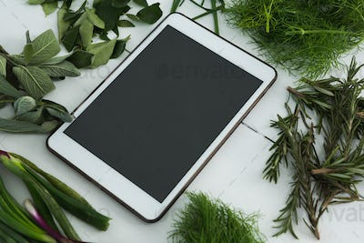 Various herbs with digital tablet on white background