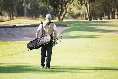Rear view of sportsman walking with his golf bag