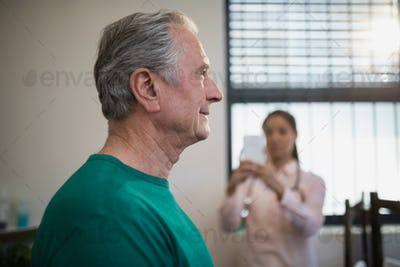 Side view of senior male patient with female therapist photographing against window