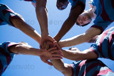 Low angle view of rugby team holding hands
