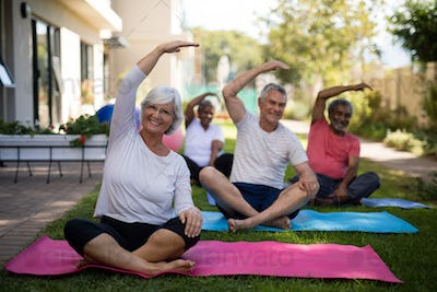 Senior people exercising with hands raised