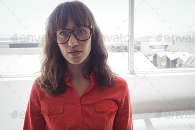Serious female designer standing by window in office