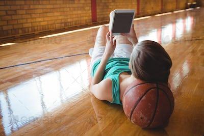 Woman using digital tablet while lying on floor