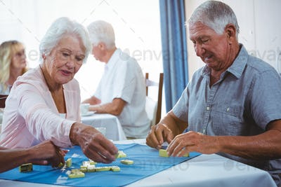 Senior persons enjoy playing domino