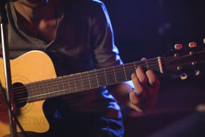 Mid section of male guitarist at music concert