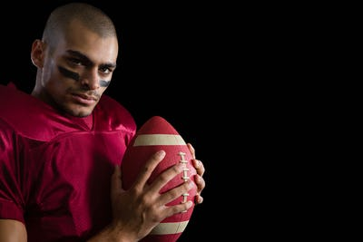 Determined American football player holding a football with both his hands