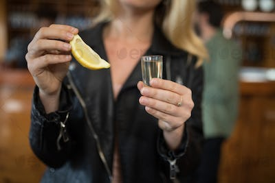 Woman holding tequila shot and lemon wedge in bar