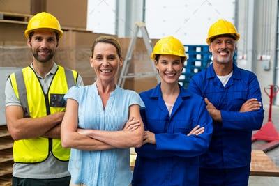 Portrait of warehouse manager and worker standing together with arms crossed