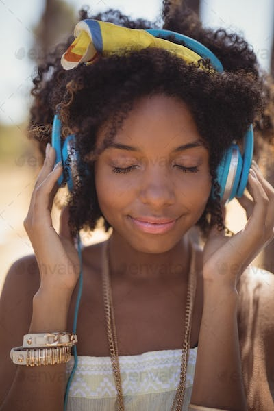 Close of young woman with eyes closed listening music