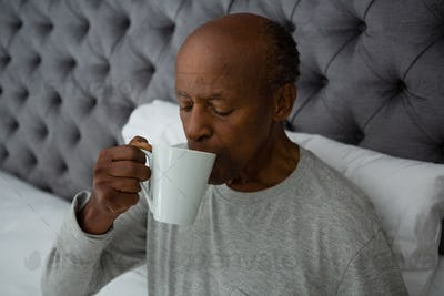Senior man drinking coffee while sitting on bed