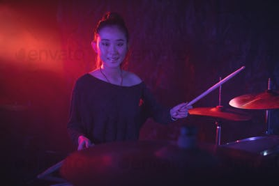 Portrait of smiling female drummer playing drum kit in nightclub