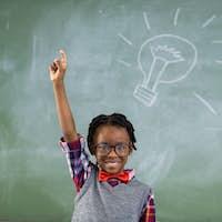 Portrait of schoolboy raising his hand against chalkboard