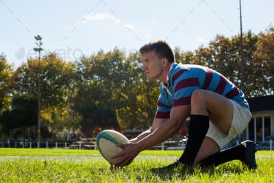 Side view of man getting ready to kick for goal