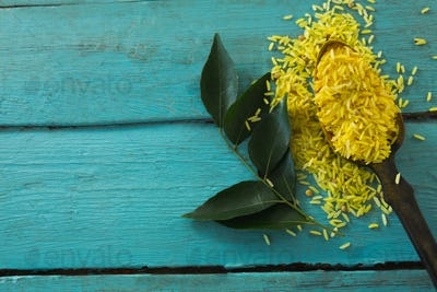 Raw organic yellow rice and curry leaves on wooden table