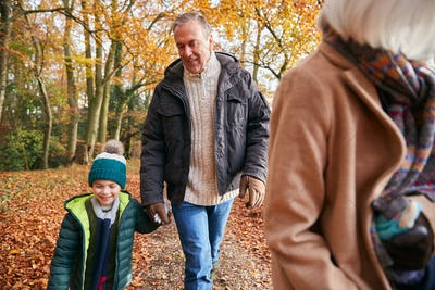 Grandparents With Grandchildren Enjoying Walk Along Autumn Woodland Path Together