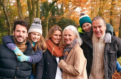 Portrait Of Smiling Multi-Generation Family Walking Along Autumn Woodland Path