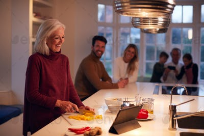 Senior Woman Preparing Meal For Family From Recipe On Digital Tablet