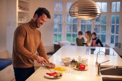Man In Kitchen At Home Preparing Ingredients For Family Meal