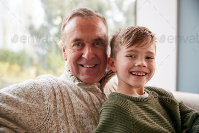 Portrait Of Grandson Sitting On Sofa At Home With Grandfather