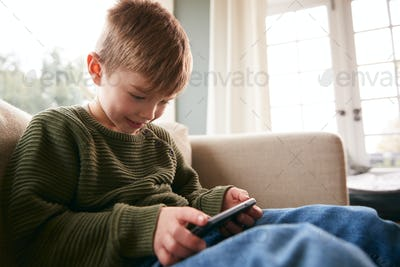 Young Boy On Sofa At Home Having Fun Playing Game On Mobile Phone