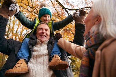 Grandparents With Grandson Enjoying Walk Along Autumn Woodland Path Together