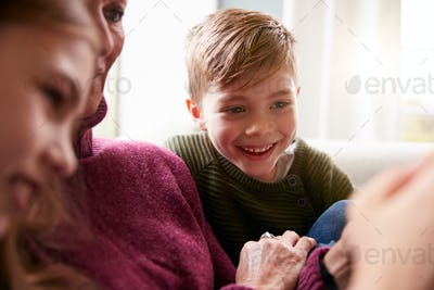 Grandchildren On Sofa At Home Showing Grandmother How To Use Mobile Phone