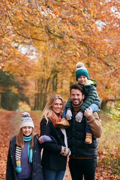 Portrait Of Family Walking Along Autumn Woodland Path With Father Carrying Son On Shoulders