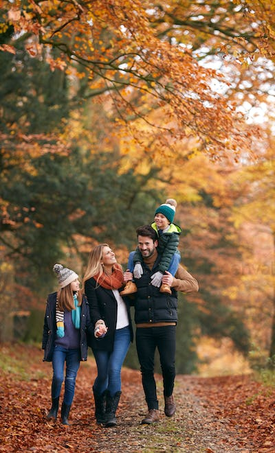 Family Walking Along Autumn Woodland Path With Father Carrying Son On Shoulders
