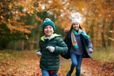 Two Smiling Children Having Fun Running Along Path Through Autumn Woodland Together