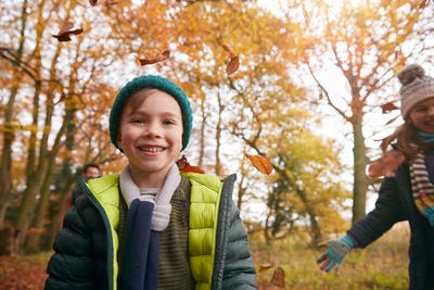 Children Throwing Leaves As Family Walk Along Autumn Woodland Path