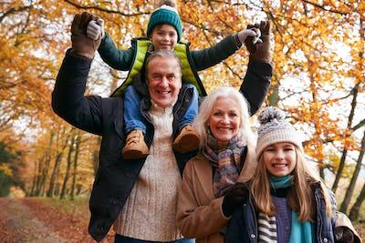 Portrait Of Grandparents With Grandchildren Enjoying Walk Along Autumn Woodland Path Together