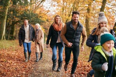 Multi-Generation Family Enjoying Walk Along Autumn Woodland Path Together