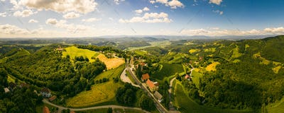 Aerial panorama of of green hills and vineyards with mountains in background. Austria vineyards