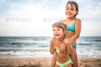 Two cute positive little girls sisters