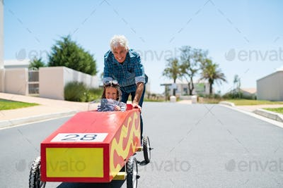 Grandfather playing with grandson on a big toy car