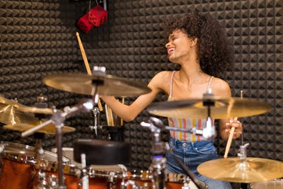 Young black female drummer in a recording studio