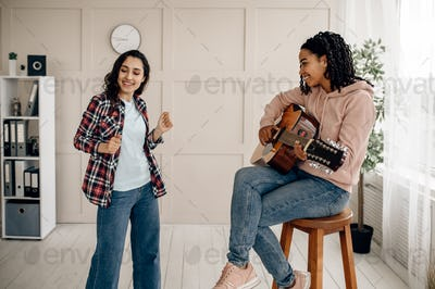 Funny women play the guitar and dancing at home