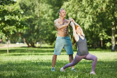 Adjusting yoga pose of woman