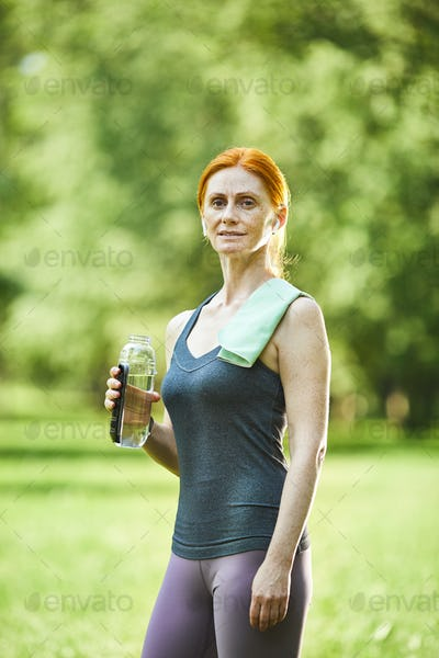 Redhead woman with bottle of water