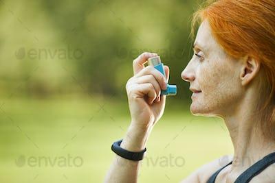 Redhead woman using inhaler outside