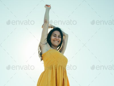 Portrait of young brunette woman in yellow dress. Looking downward straight to camera view