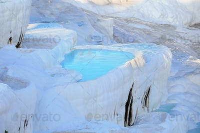 Travertine terraces with clear blue water in Pamukkale
