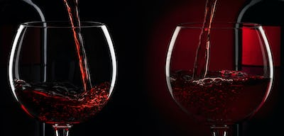 Pouring red wine into the glass against red black background