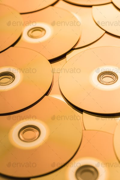 CDs and DVDs in golden tone as background
