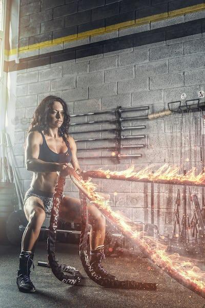 Sporty brunette female exercising with burning battle rope.